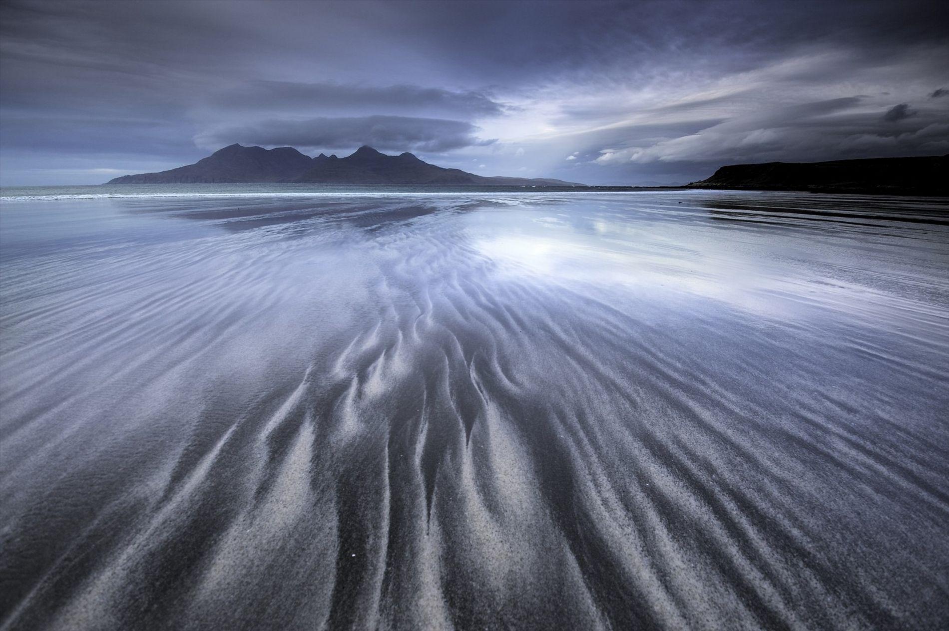 """Die Aussicht auf die Insel Rum von der Laig Bay auf der Insel Eigg aus. Das Licht tanzt auf dem Wasser, das den breiten, sacht abfallenden Strand formt. Er besteht aus weißem Muschelsand, der von schwarzem Basaltsand durchzogen ist. Dieser wird aus dem vulkanischen Herzen der Insel in Richtung Ufer gespült. Auf die Small Isles oder """"Kleinen Inseln"""" (Eigg, Muck, Rum und Canna) kann mit der Fähre von Mallaig aus übergesetzt werden."""