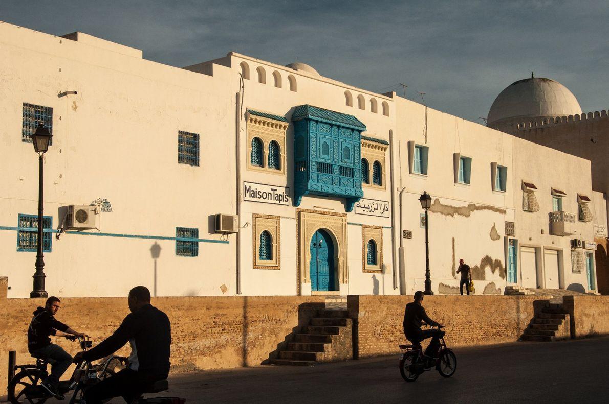 In der tunesischen Stadt Kairouan radeln Fahrradfahrer an einem Teppich- und Souvenirladen mit blauen Türen vorbei. ...