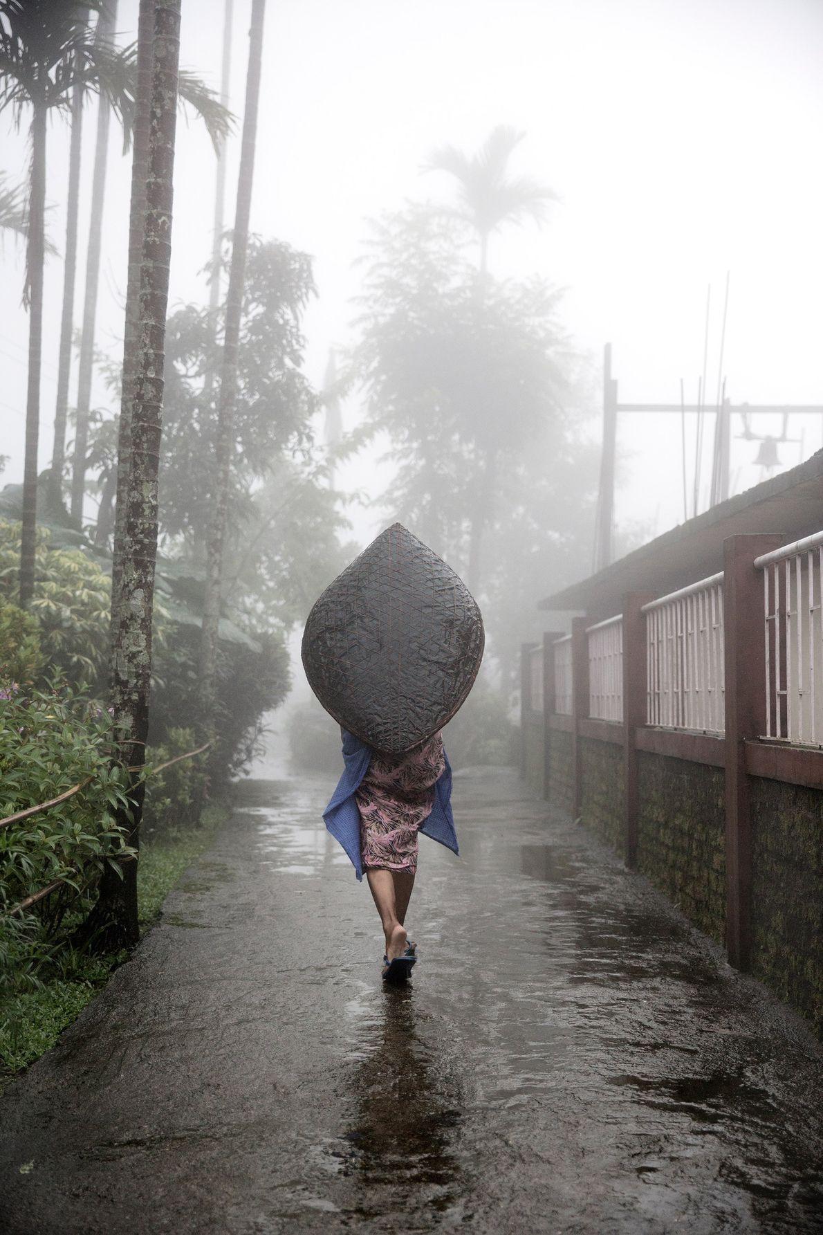 Eine Frau benutzt einen traditionellen Regenschirm der Khasi