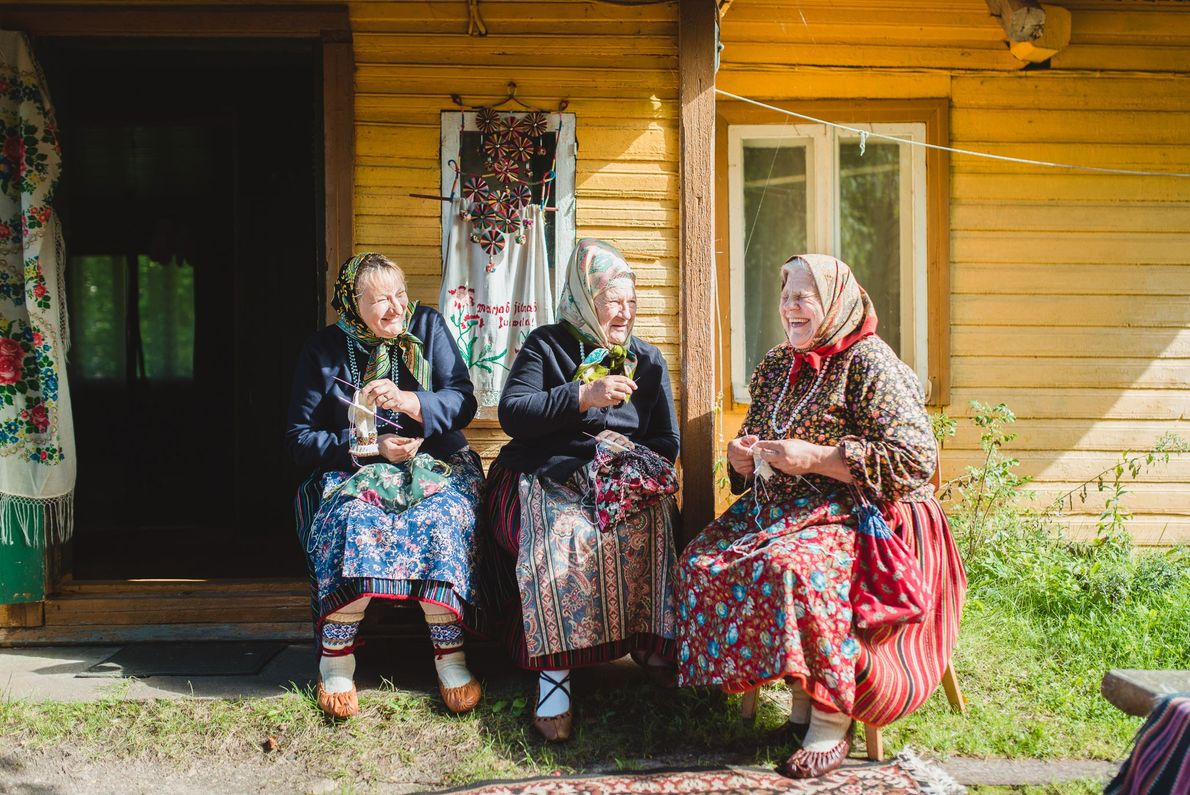 Einheimische auf Kihnu in traditionellen Röcken warten auf eine Gruppe japanischer Touristen. An den gemusterten Röcken ...
