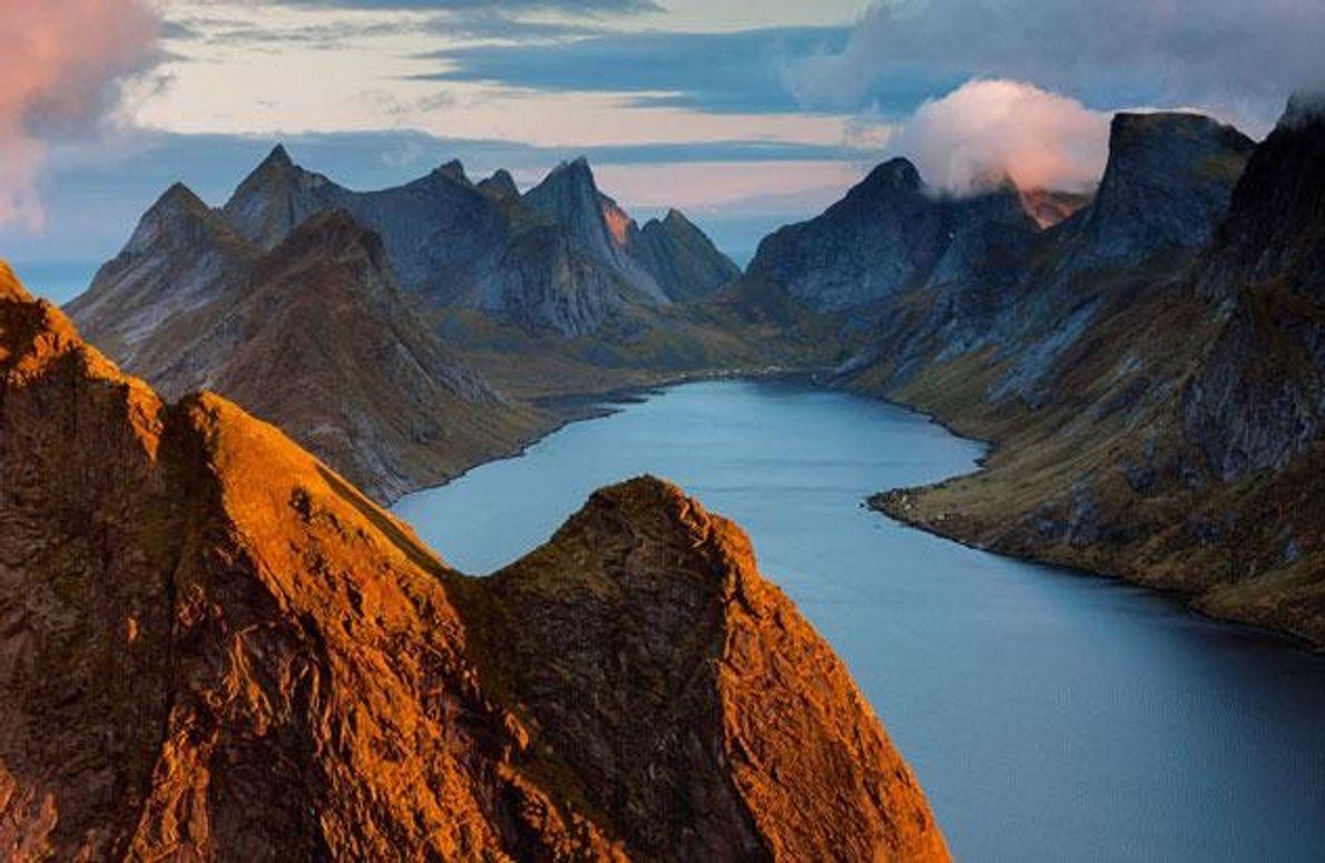 Umschlossen von den schroff aufragenden Bergen der norwegischen Lofoten leuchtet der Kirkefjord in der Mitternachtssonne.