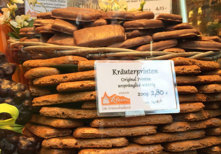 Gestapelte Printen locken Besucher in die Printenbäckerei Klein. In einem Körbchen ganz oben liegen mit Schokolade ...