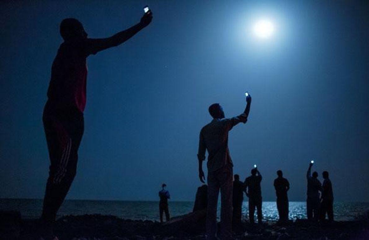 Migranten an der Küste von Dschibuti versuchen, Funksignale von Verwandten aus Somalia aufzufangen. Wer auswandert, will …