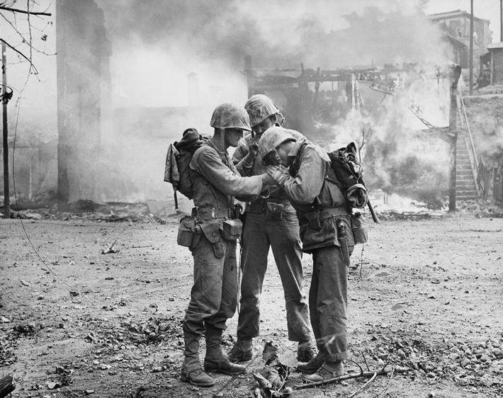 US-Soldaten reichen im September 1950 inmitten schwelender Ruinen im südkoreanischen Seoul ein Feuerzeug herum, um ihre ...