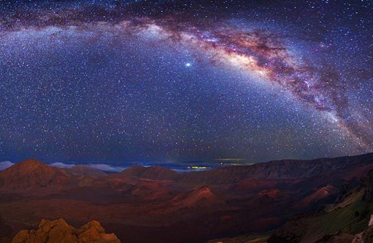 Hinter Schleiern von kosmischem Staub wölbt sich die Milchstraße über Hawaiis Vulkanlandschaft.