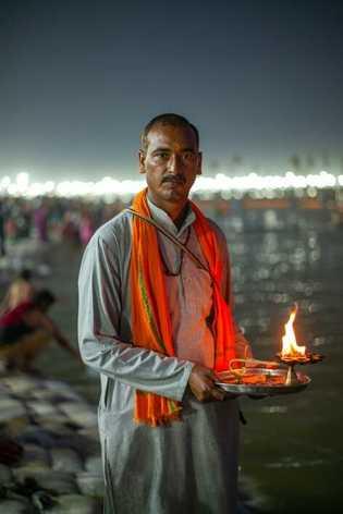 Ein Pilger entzündet am Abend eine Flamme.