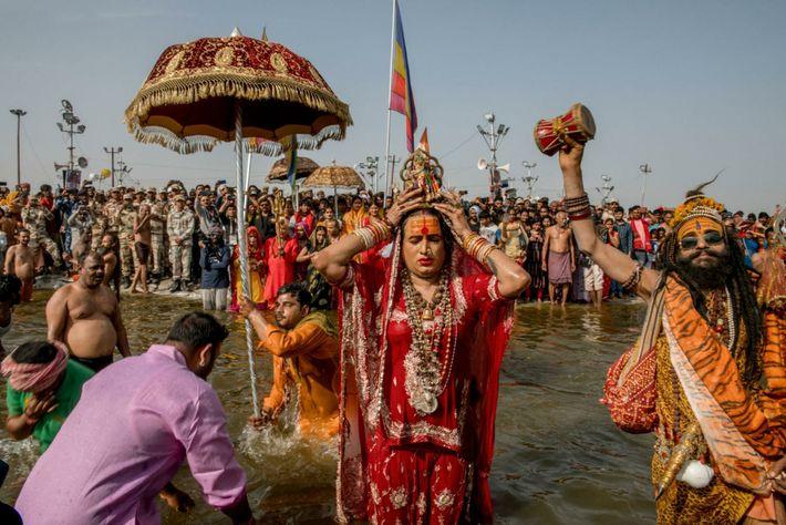 Laxmi Narayan Tripathi betet zu Lord Shiva, während sie ein heiliges Bad im Fluss Ganges nimmt. ...