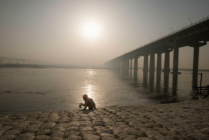 Ein Sadhu sammelt während der Kumbh Wasser aus dem Ganges.