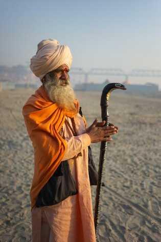 Ein Sadhu betet am Ufer des Ganges in Richtung der Sonne.