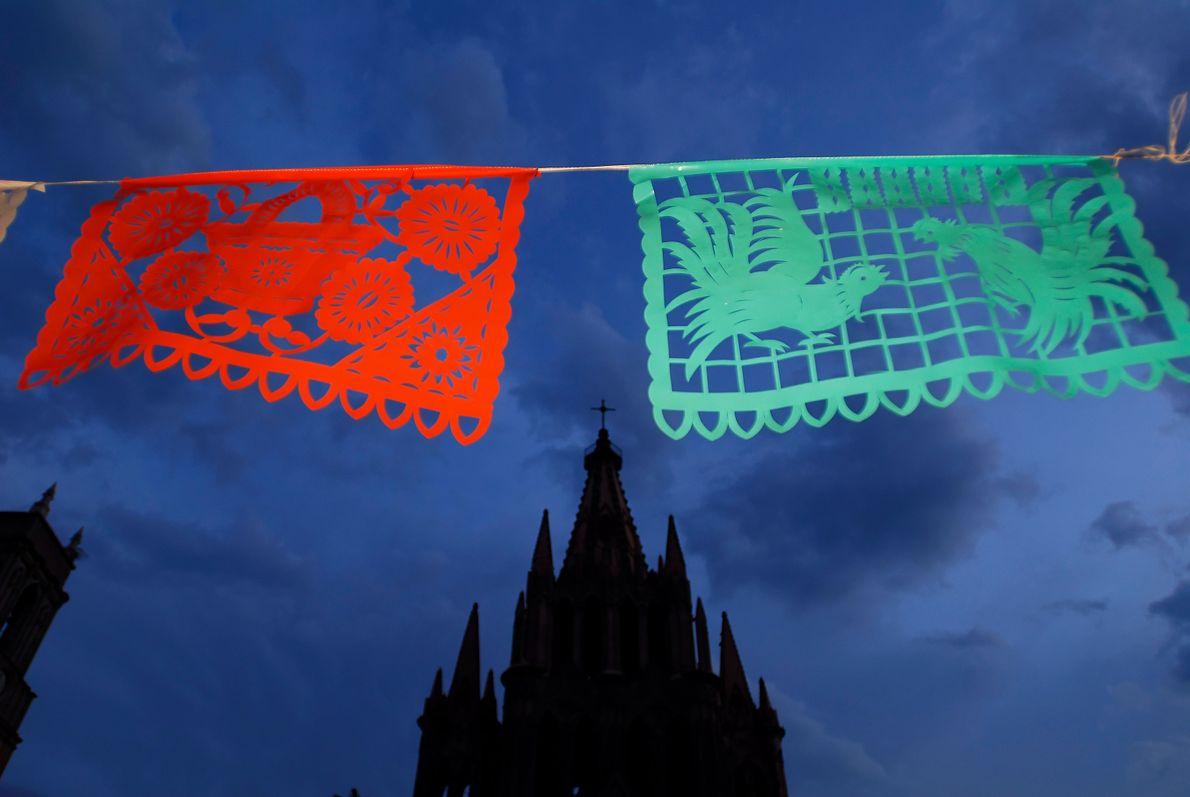 Papel picado, durchlöcherte Papiere, wehen in San Miguel de Allende im Wind. Man sieht die Papierkunstwerke ...