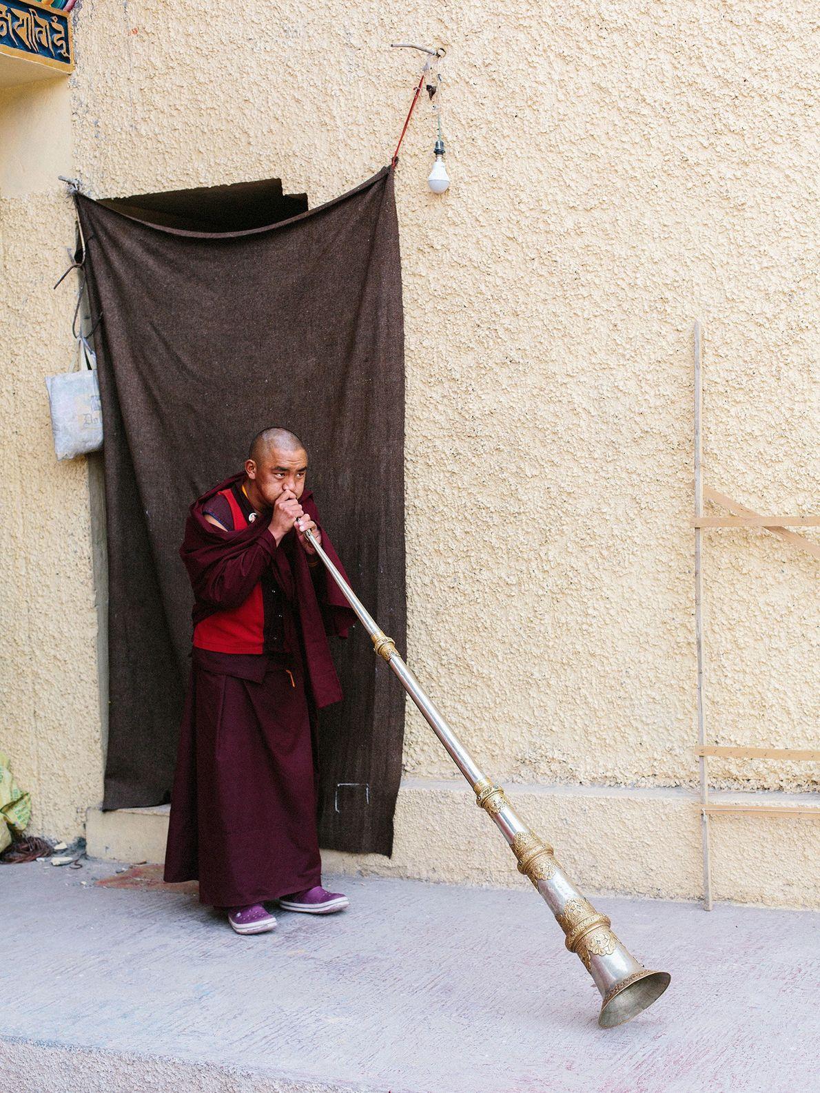 Ein junger Mönch des Klosters Karma Dupgyud Choeling bläst eine Dungchen, ein zeremonielles Blechblasinstrument.