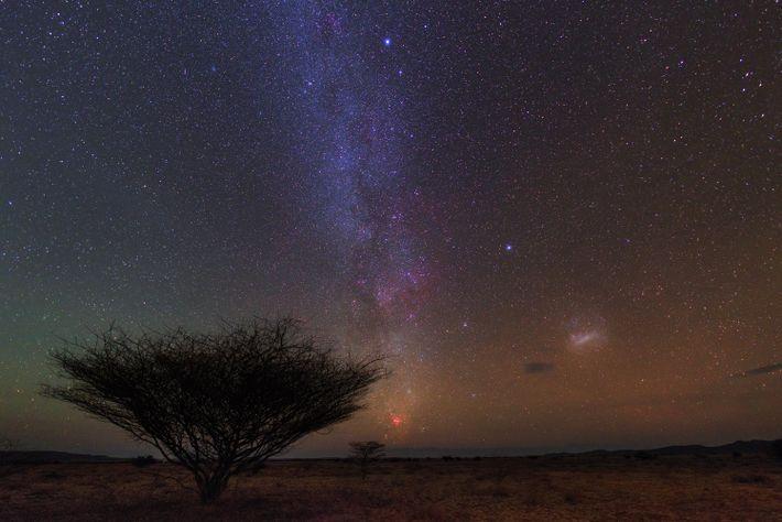 Die südliche Milchstraße, die Große Magellansche Wolke und der Carinanebel (die rötliche Wolke am Horizont) vom ...
