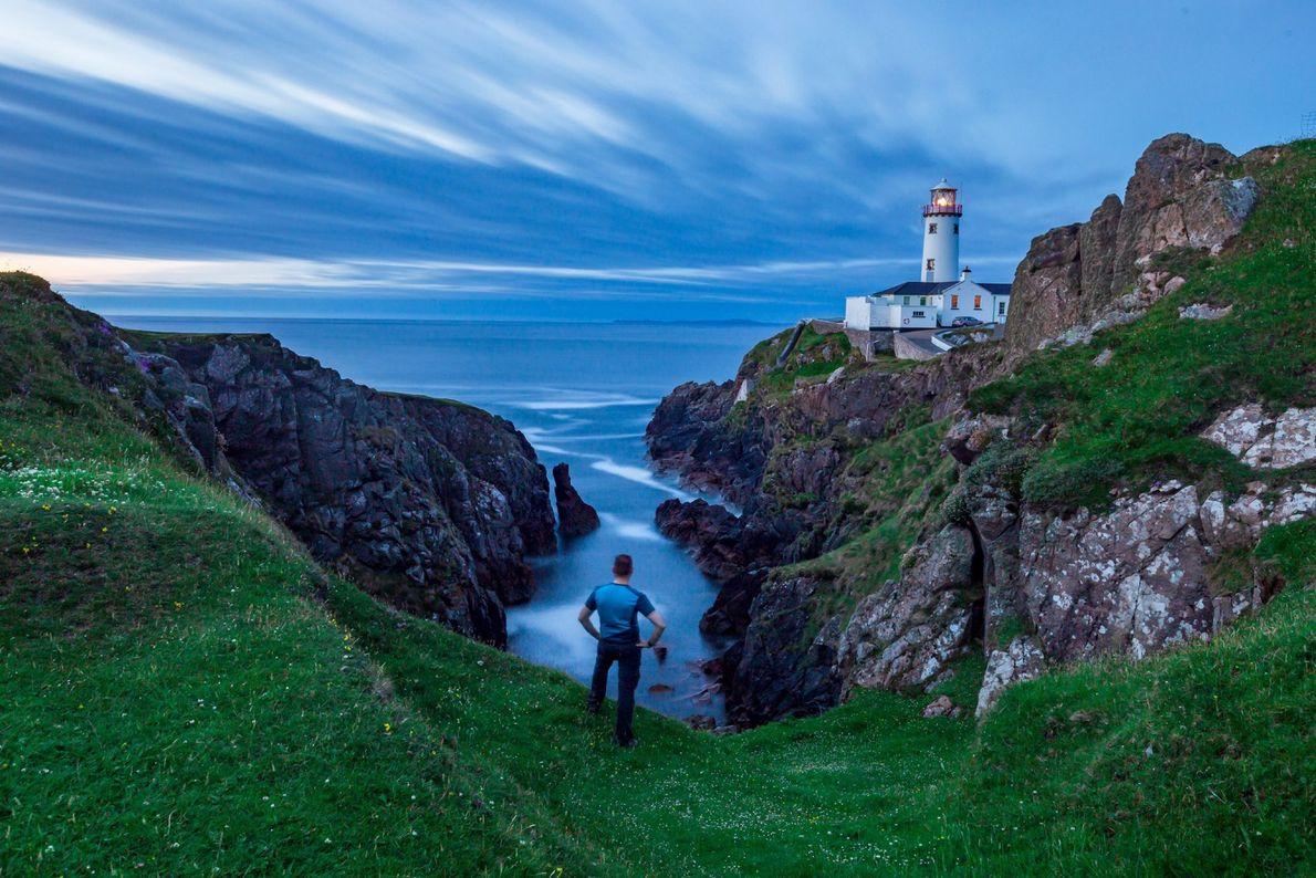 Wolken und das blaue Meer rahmen den 202 Jahre alten Leuchtturm Fanad Head auf Donegal am ...