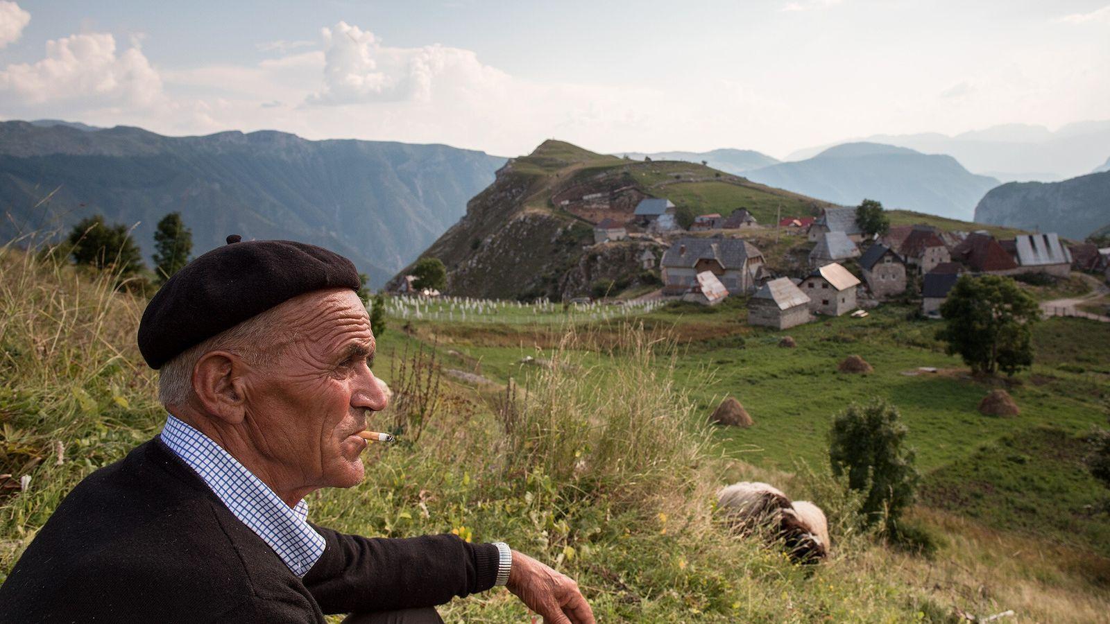 Ein Mann macht eine Zigarettenpause und genießt den Blick auf Lukomir.