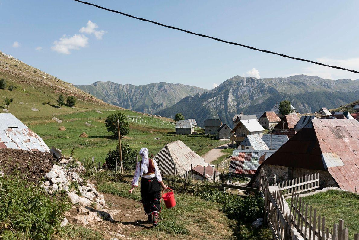 Eine Frau geht durch das Dorf, um ihre häuslichen Arbeiten zu verrichten.