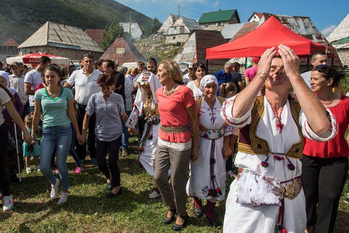 Dorfbewohner und Besucher führen einen traditionellen Kreistanz auf.