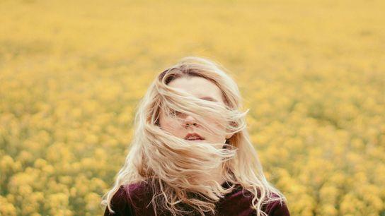 Frau auf Blumenwiese, das Gesicht ist teils von Haaren versteckt
