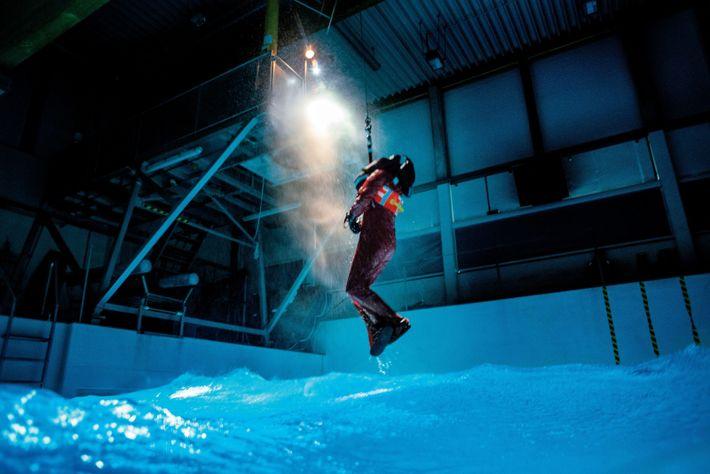 Seilwinde zieht erschöpften Teilnehmer aus dem Pool, nachdem dieser durch einen simulierten Sturm schwamm
