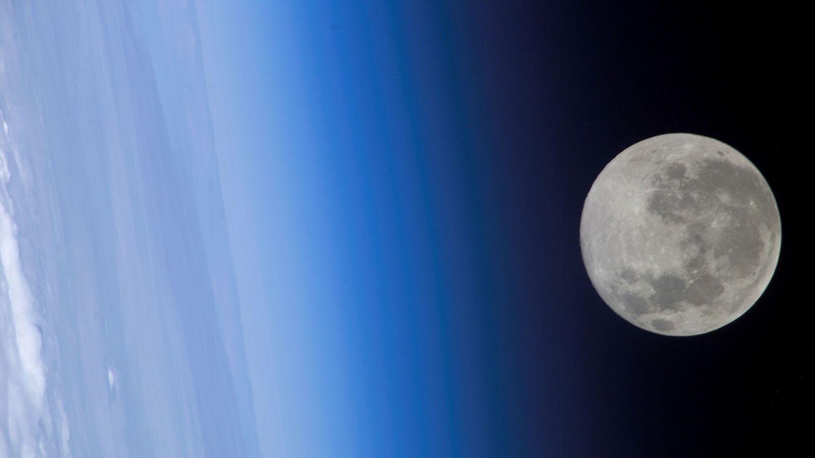 Auf diesem Bild, das von der ISS aufgenommen wurde, scheint der Vollmond die Erdatmosphäre zu streifen.
