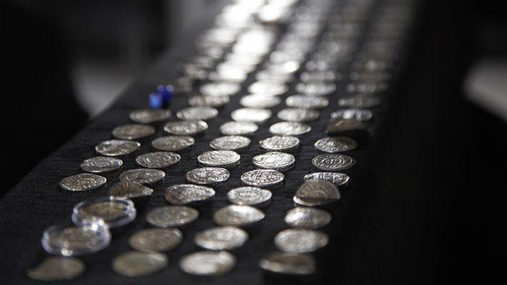 Antike Münzen, aufgereiht auf einem dunklen Untergrund