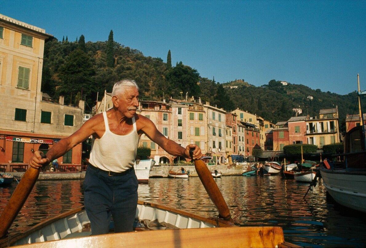Ein Mann rudert sein Boot in den Hafen von Portofino in Nordwest-Italien.