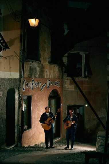 Nach Einbruch der Dunkelheit: Straßenmusiker spielen im Straßenlaternenlicht in Portofino, 1965.
