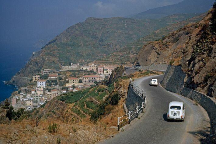 Fiats unterwegs auf einer kurvigen Bergstraße, hinunter zum Stadtkern von Riomaggiore, Teil der Cinque Terre-Region.