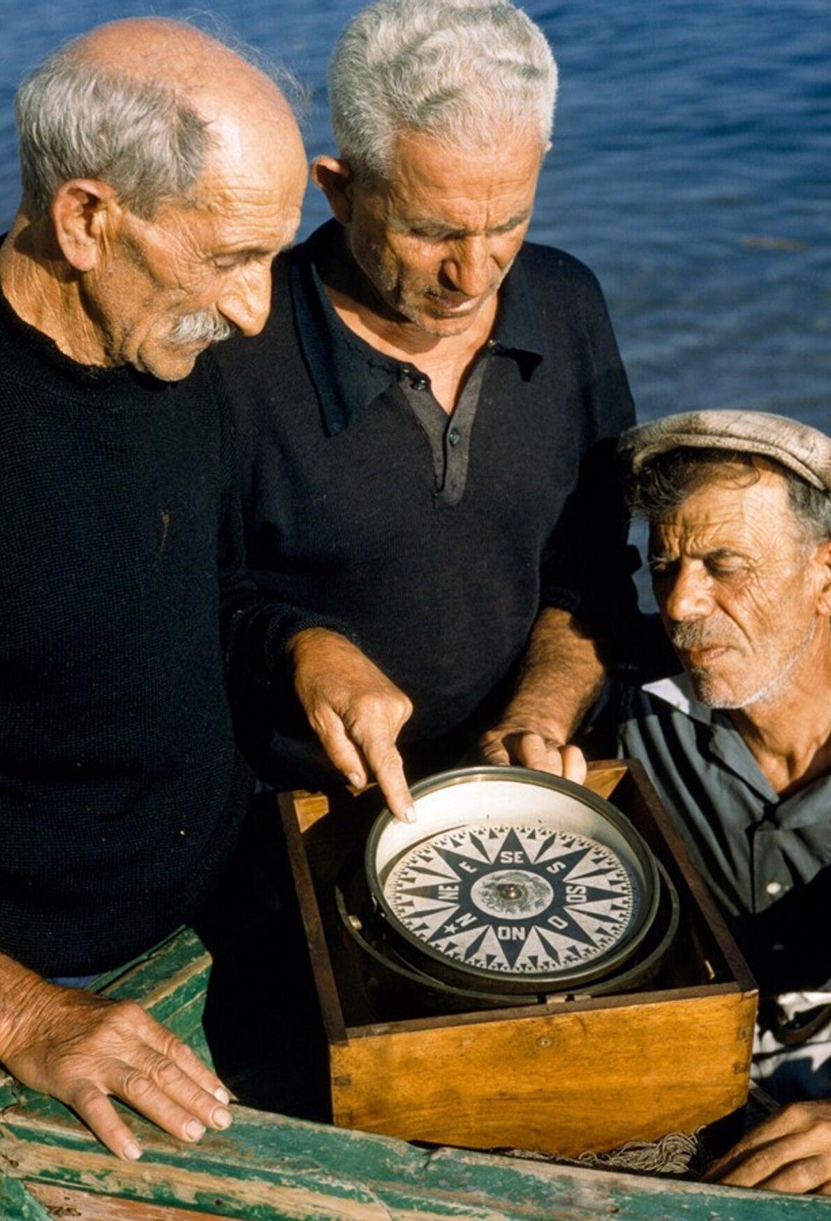 Drei Fischer betrachten einen antiquierten Marine-Kompass vor der Amalfiküste, 1959.