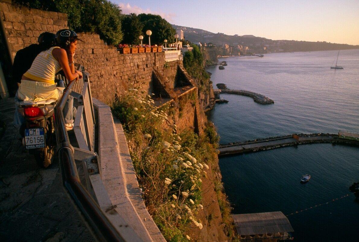 Junge Leute schauen sich den Sonnenuntergang über der Bucht von Neapel nahe Sorrento von ihren Rollern ...