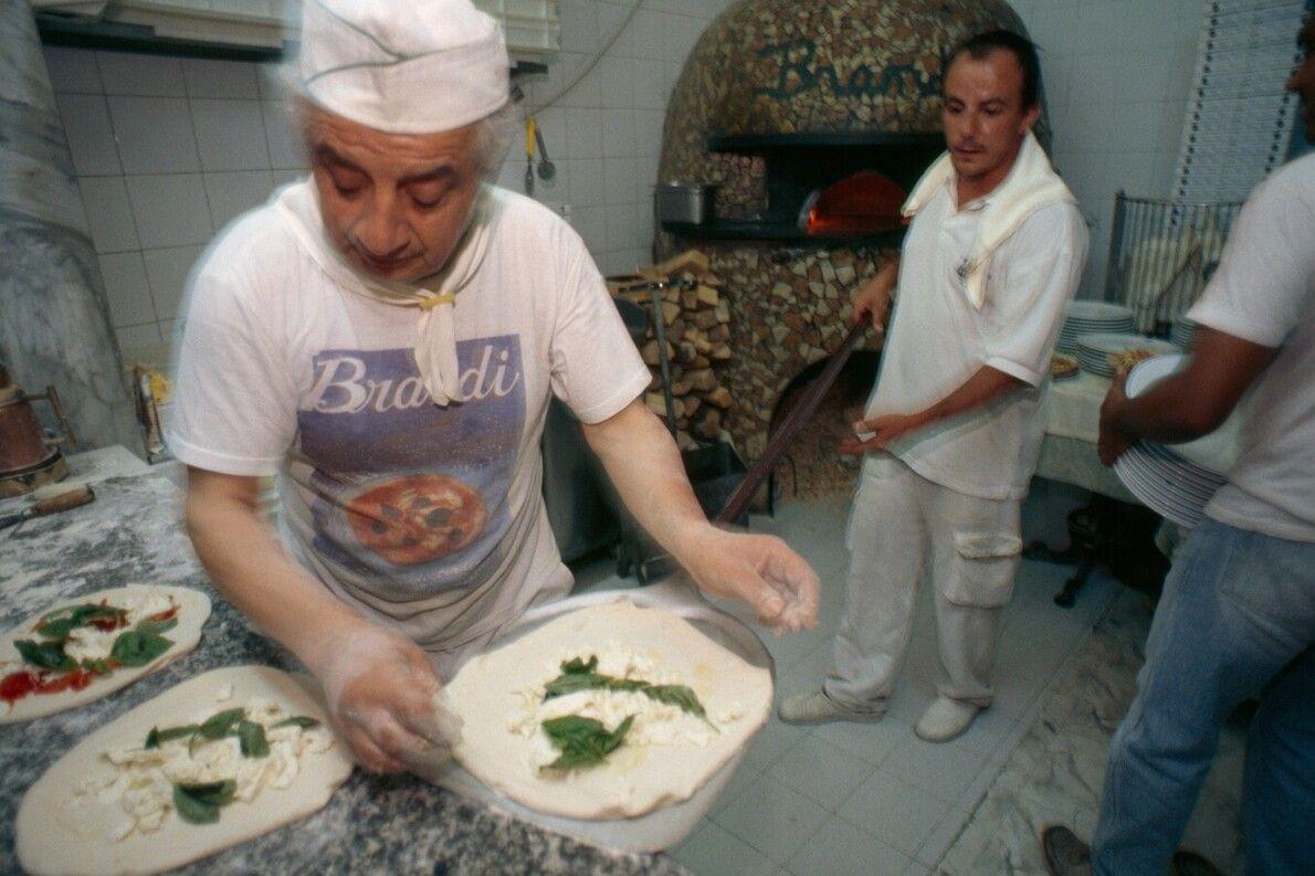 """Pizzabäcker, im italienischen """"Pizzaioli"""", schieben Pizza in einen Holzofen in Neapel."""