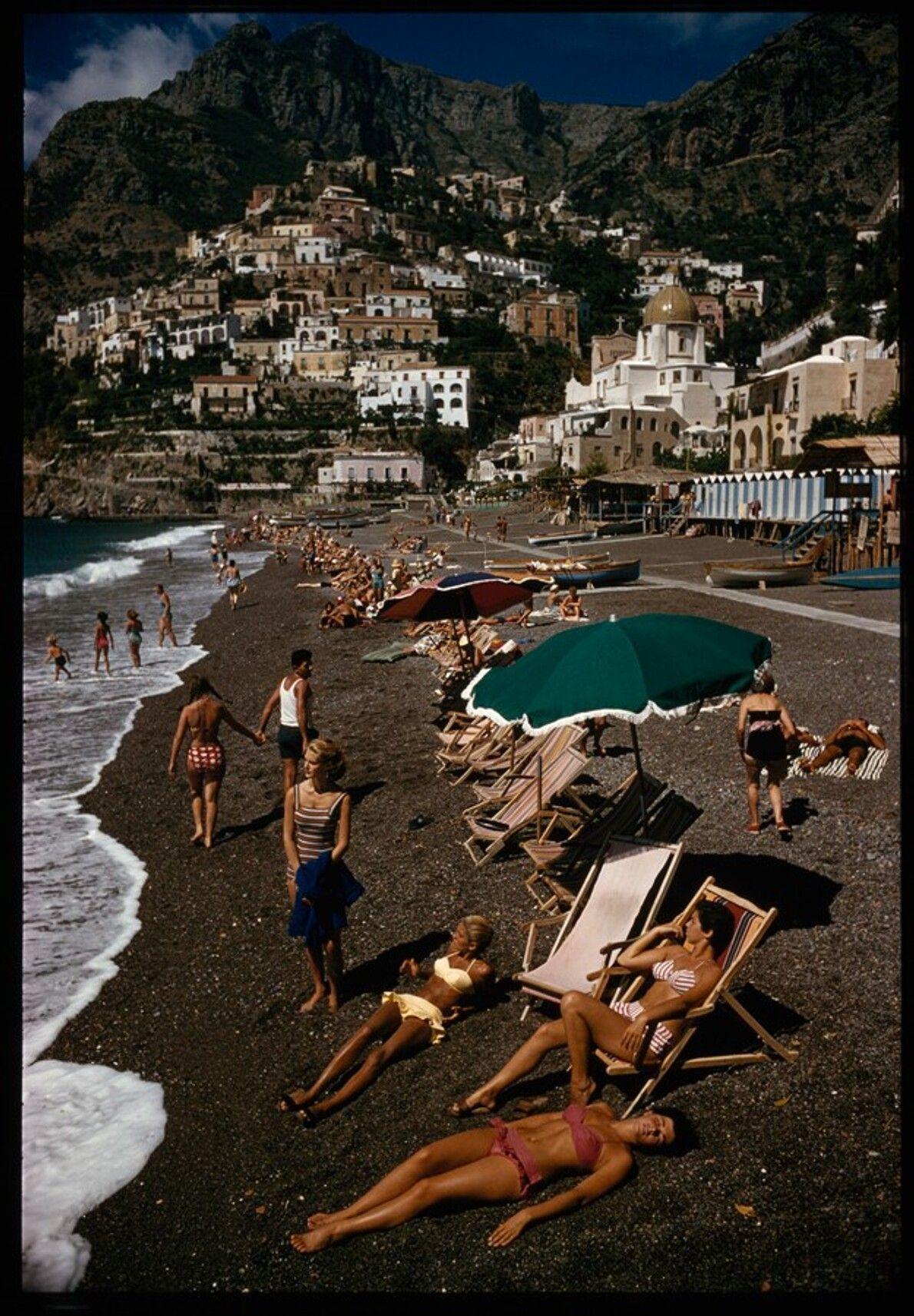 """Sonnenanbeter sonnen sich neben den Gebäuden der """"vertikalen Stadt"""" Positano, 1959."""