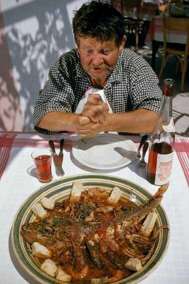 In der Hafenstadt Positano bereitet ein Mann den Fisch fürs Abendessen vor, den er gefangen hat, ...