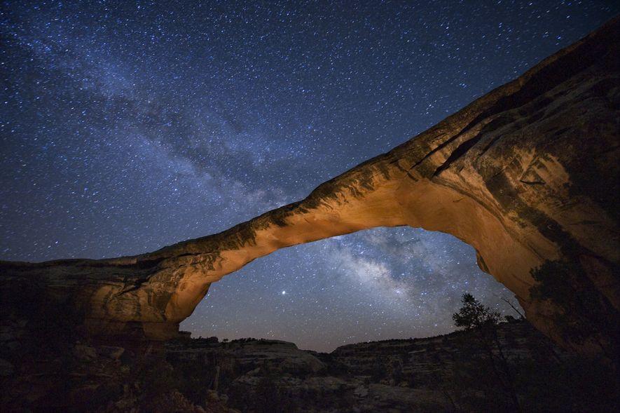 Ein spektakulärer Sternenhimmel leuchtet über der Owachomo Bridge im Natural Bridges National Monument in Utah, USA.