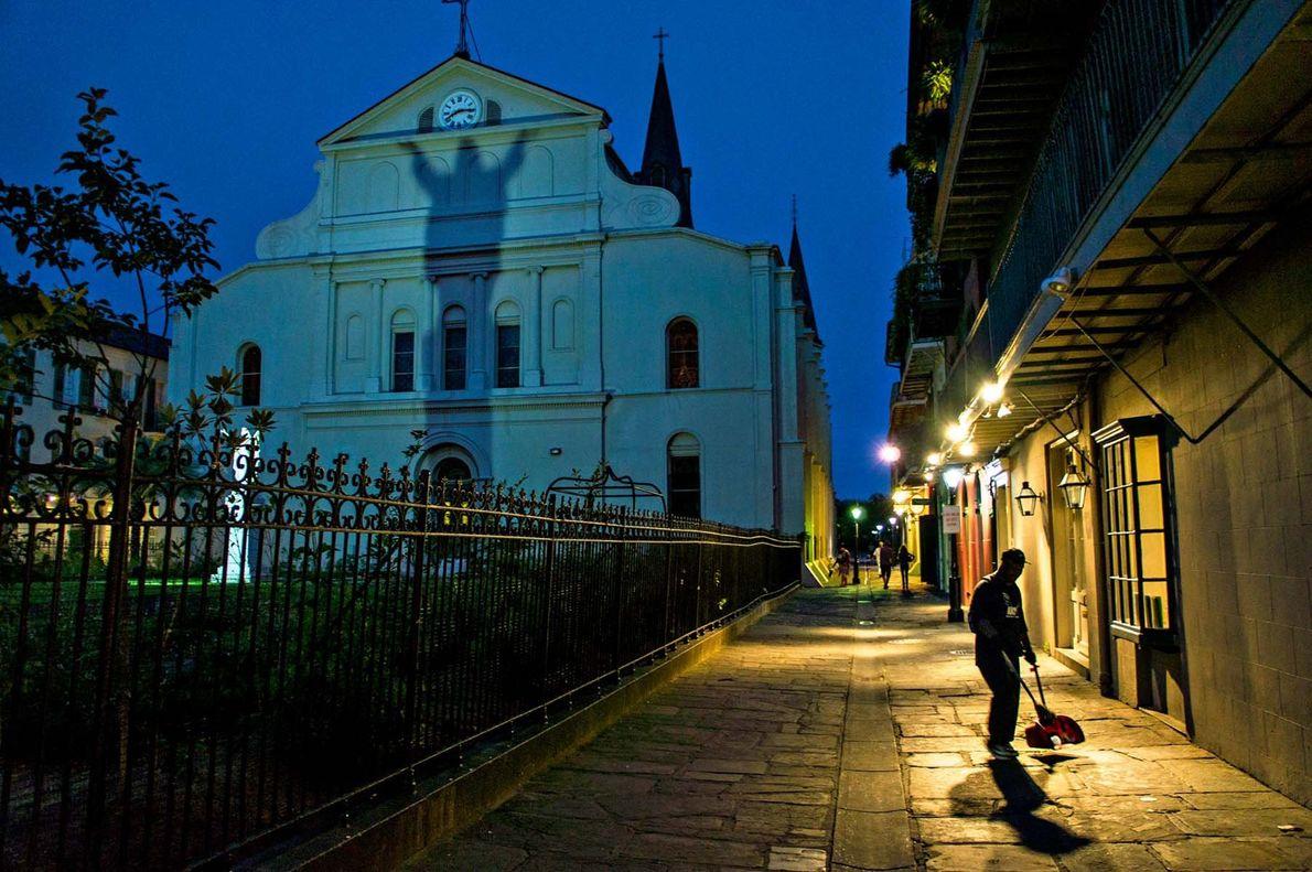 Ein Mann kehrt die Straßen, als sich der Abend über die St. Louis Cathedral in New ...