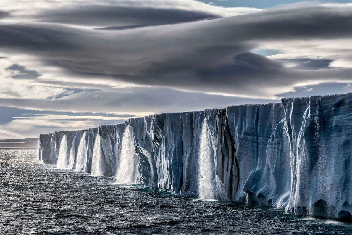 Schmelzwasser rinnt von einer Eiskappe auf der Insel Nordostland im norwegischen Archipel Spitzbergen.