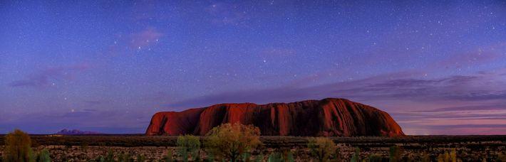 Die Farben des Sonnenuntergangs hängen noch am Himmel, als die ersten Sterne über dem Uluṟu-Kata-Tjuṯa-Nationalpark in ...