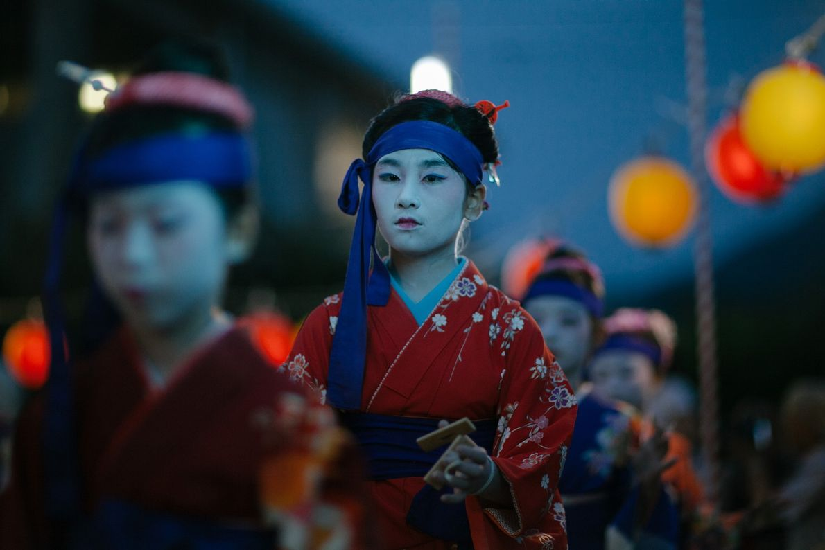 A girl dressed as a geisha stands in line at the beginning of the Obon dance ...