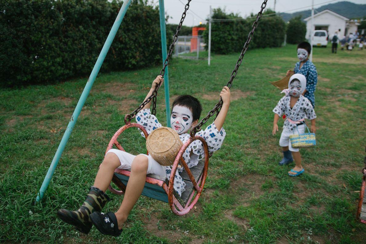 """Als """"betrunkene Fischer"""" verkleidete Kinder spielen während des O-bon-Fests im Freien."""