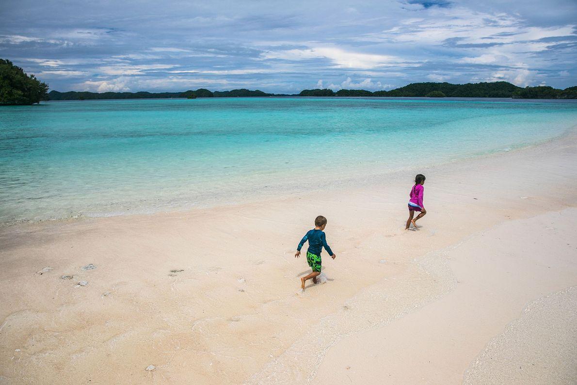 Zwei palauische Kinder rennen einen Strand der Rock Islands entlang.