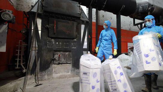 Arbeiter in Kiew in der Ukraine entsorgen gebrauchte Masken und Handschuhe in einem Verbrennungsofen.