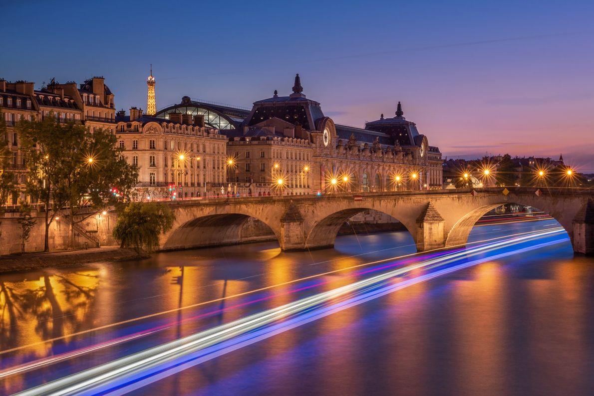 Der hell erleuchtete Eiffelturm erstrahlt hinter dem Musée d'Orsay, während ein Boot unter der Pont du ...