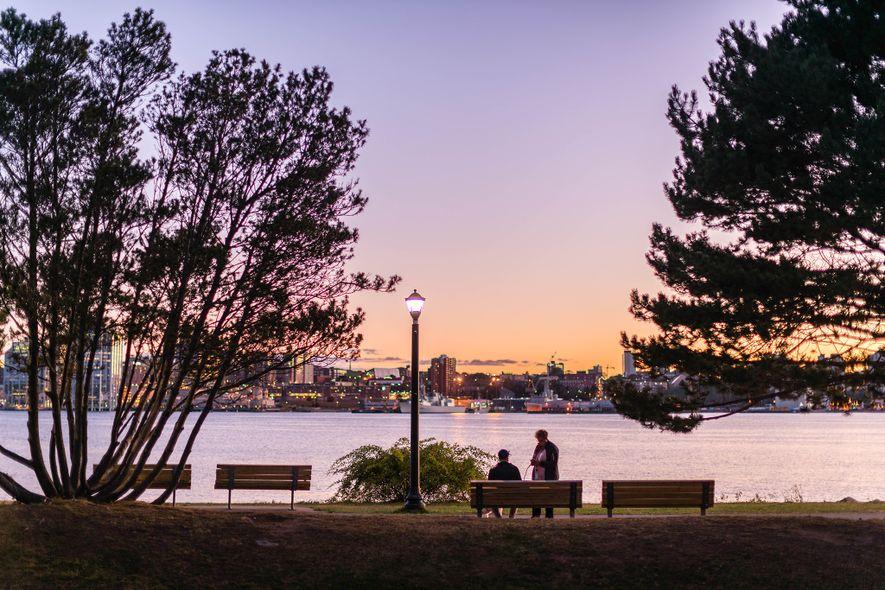 Bänke säumen die Gehwege des Ferry Terminal Park, wo Besucher die funkelnden Lichter von Halifax bewundern ...