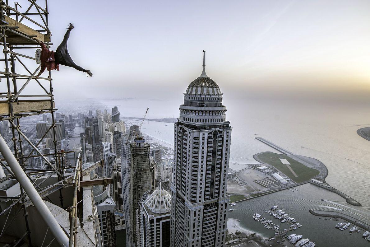 Ein Traceur – ein Parkoursportler – hängt an einem Baugerüst an einem Gebäude in Dubai, Vereinigte ...