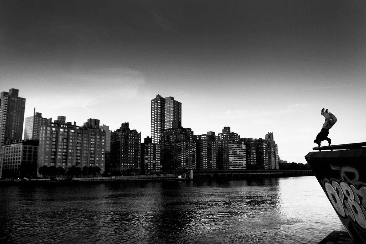 Ein Traceur machen einen Handstand auf dem New Yorker Roosevelt Island am Ufer des East River.