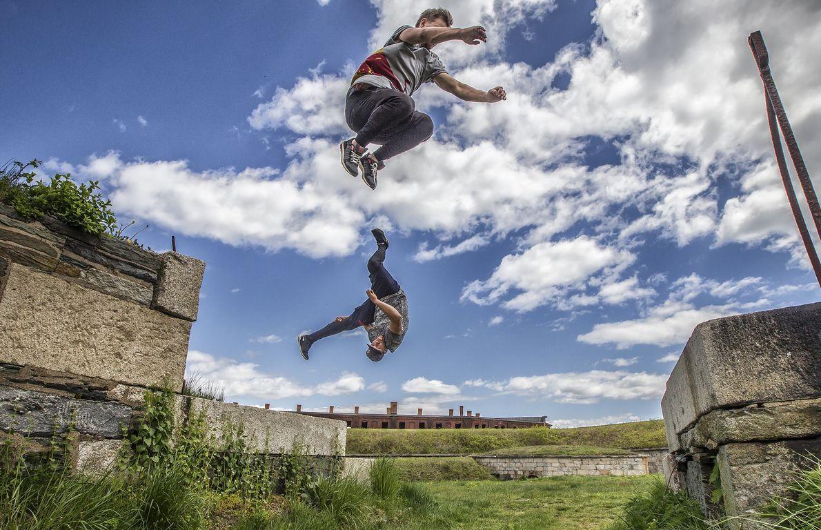 Zwei professionelle Freerunner springen zwischen Steinblöcken in Newport in Rhode Island umher. Viele moderne Parkourathleten bauen ...