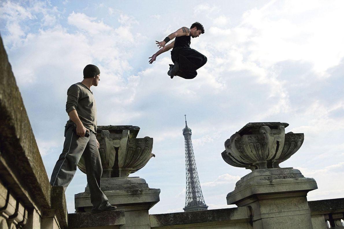 Ein Parkourläufer bewegt sich vor dem Eiffelturm in Paris an einer Wand mit Zierelementen entlang. Der ...
