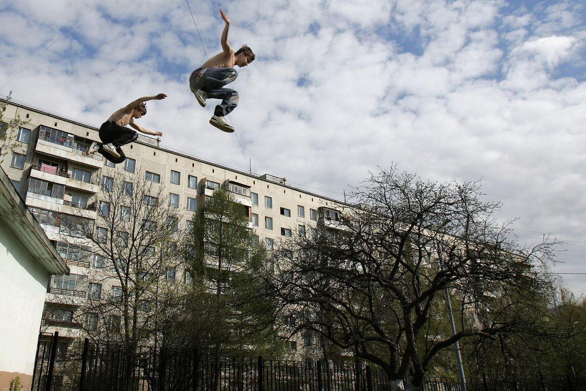 Zwei junge Menschen springen in Moskau vom Dach eines Gebäudes. Das langsame Trainieren der eigenen Fertigkeiten ...