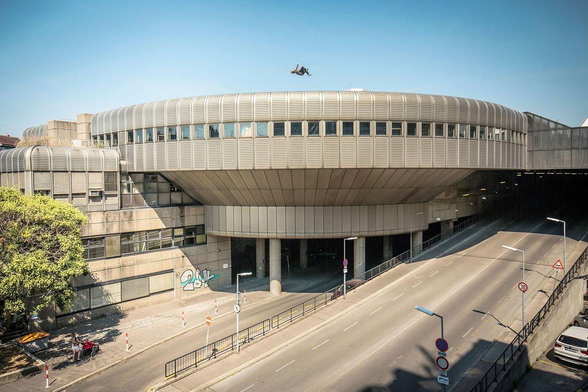 Ein professioneller Parkourläufer läuft am Rand eines Gebäudedachs in Wien entlang. Kritiker der Sportart sagen, dass ...