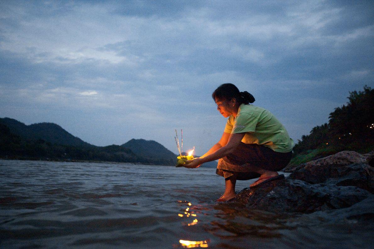 Eine Frau an einem Fluss hält eine brennende Opfergabe