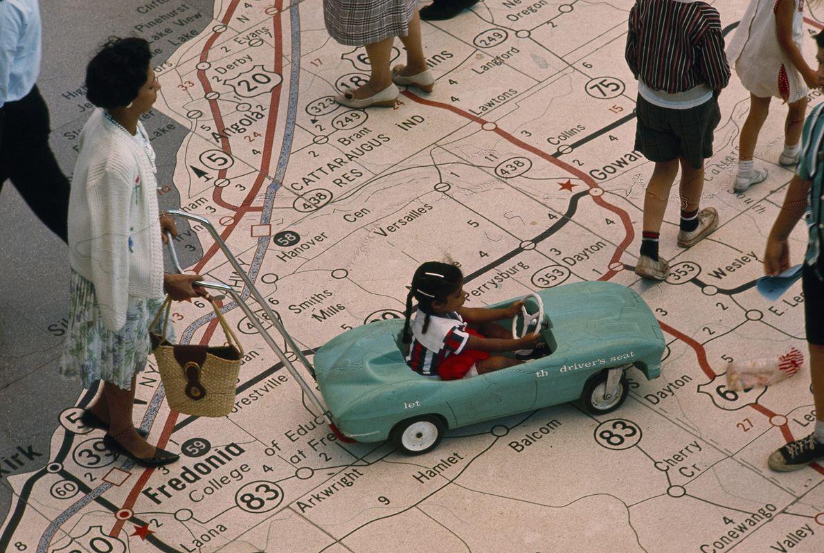 Mädchen in Spielzeugauto auf der Weltausstellung